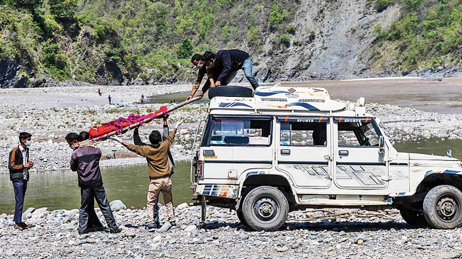 Pramila's body is taken down for  cremation on the banks of the Ganga.