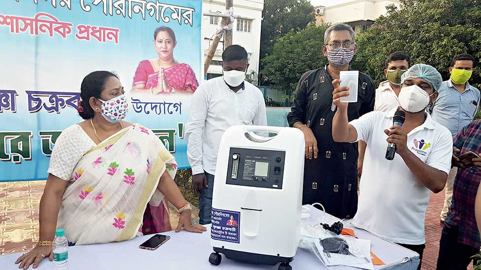 A volunteer demonstrates the use of the concentrator as ward coordinator Krishna Chakraborty looks on