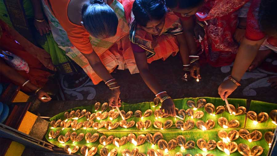 Women participate in Sandhi Puja, where 108 brass lamps are lit on banana leaves