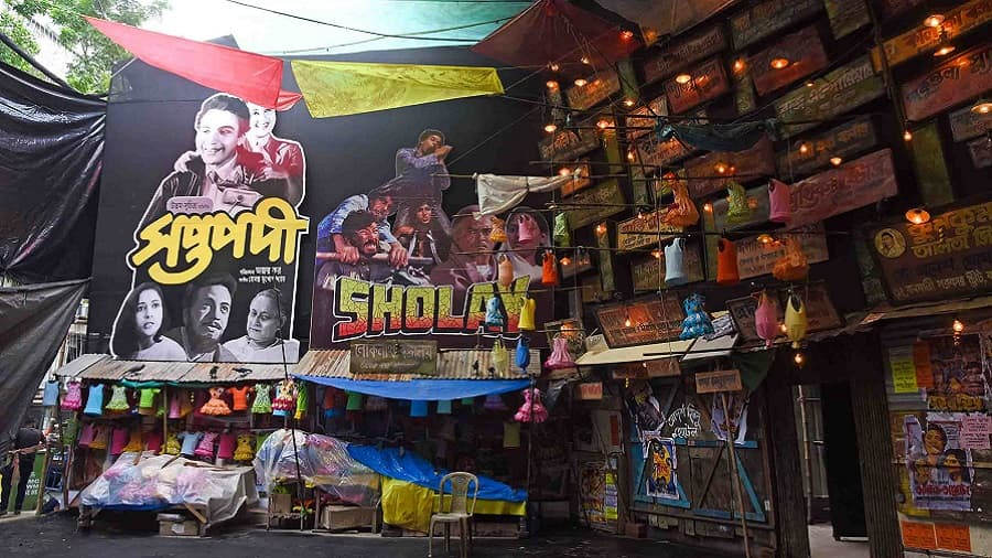 As Durga Puja is synonymous with shopping, SURUCHI SANGHA decided to recreate the indulgent world of a bazaar. The pandal encapsulates the fanaticism of a Kolkata market with colourful dresses hanging from the ceiling, film posters on the walls, plastic coverings instead of cloth, and shops for chai, kochuri and muri.