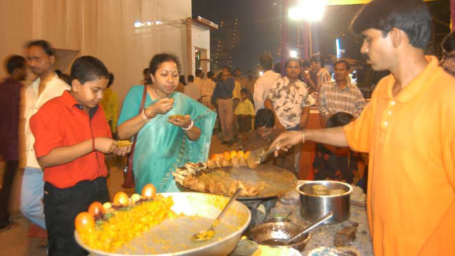 A street food stall doing brisk business during Durga Puja in a different era