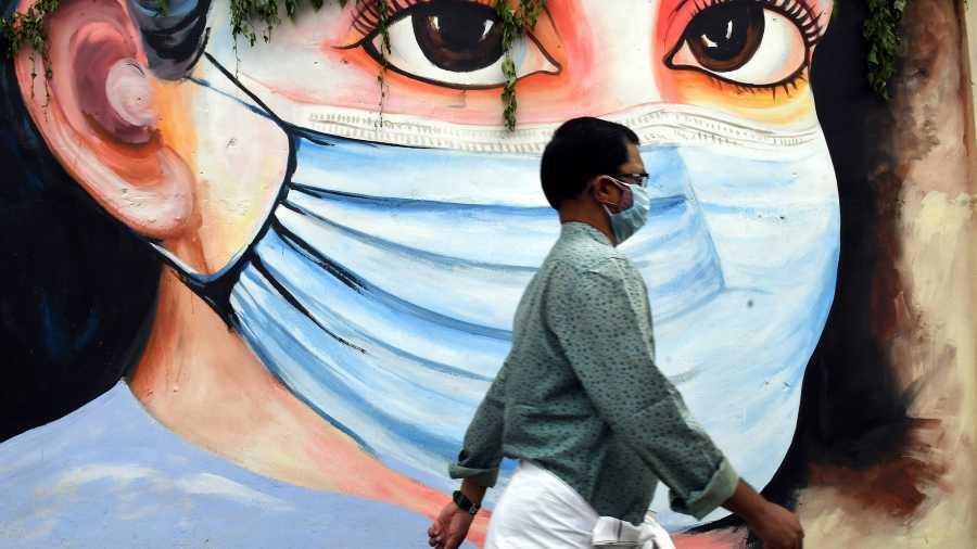 A man walks past a mural in Thiruvananthapuram, Kerala