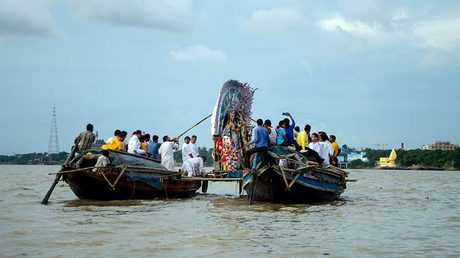 The Durga idol of Sovabazar Rajbari being carried between two boats, about to be immersed