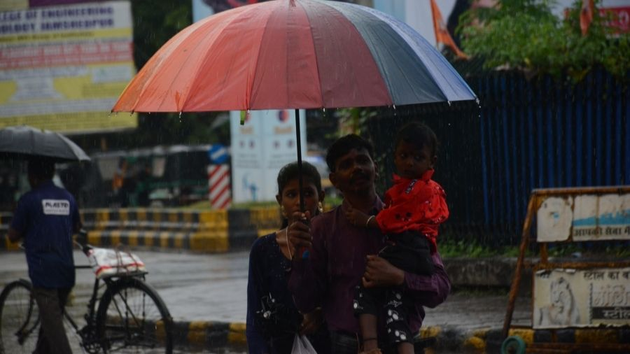 A family takes out umbrellas after being caught in sudden rain in Jamshedpur on Thursday.