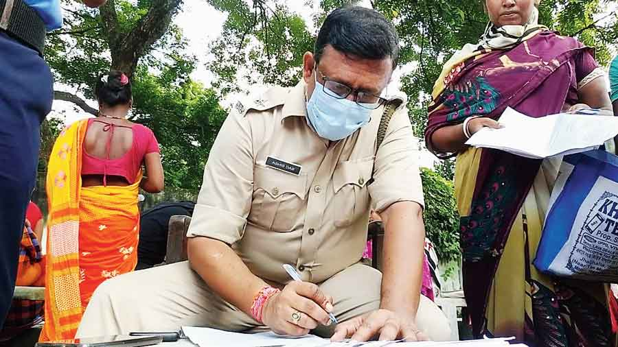 A policeman fills up a form at a Duare Sarkar camp in Kotwali, Malda, on Wednesday.