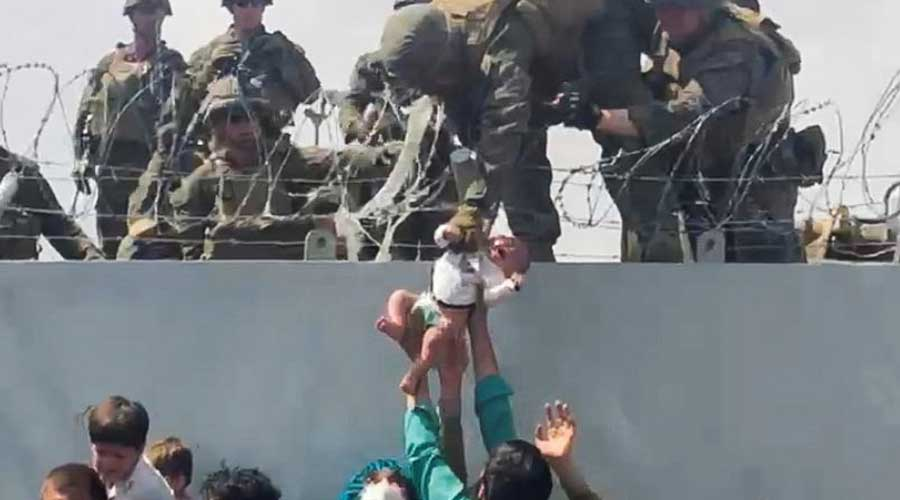 A baby is handed over to the American army over the perimeter wall of the airport for it to be evacuated, in Kabul, Afghanistan, August 19, 2021.