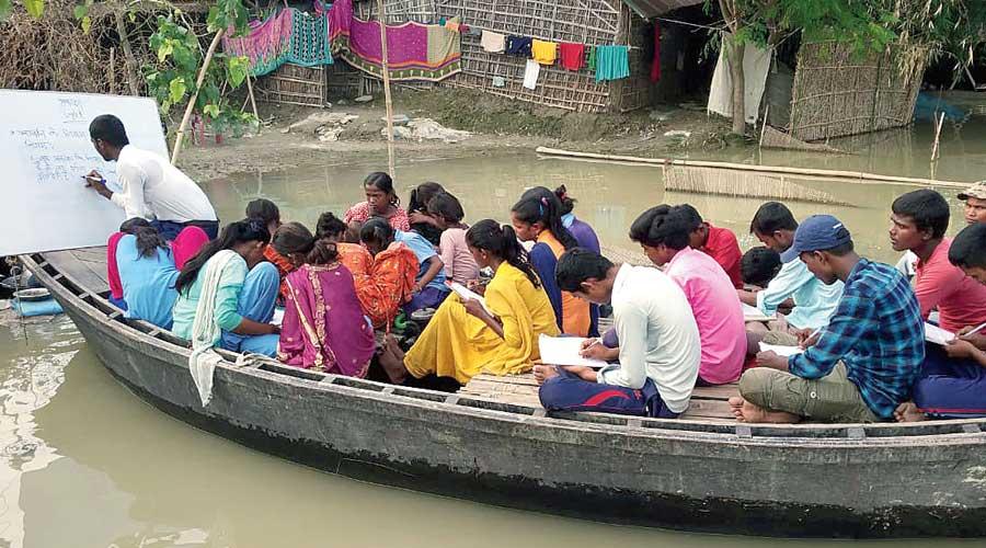 Pankaj Kumar Sah, one of three teachers, takes classes on a boat in Manihari of Katihar on Sunday