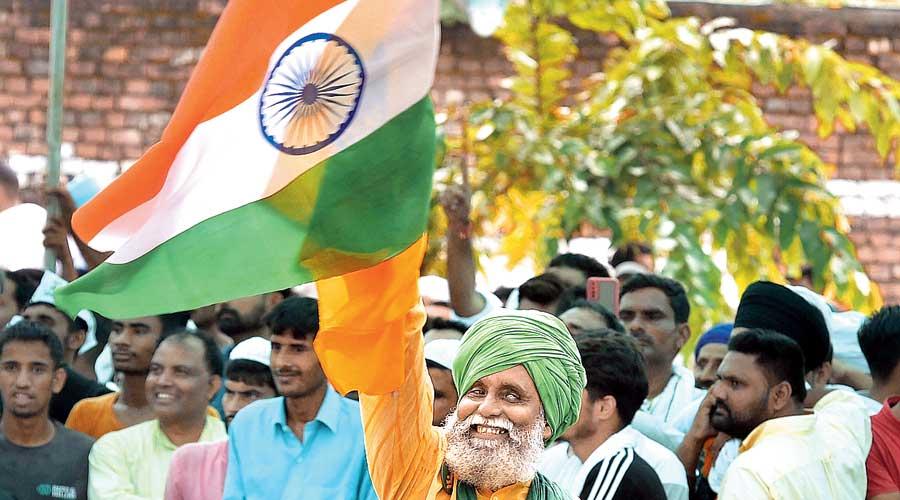 A farmer holds aloft the Tricolour at the  mahapanchayat in Muzaffarnagar on Sunday