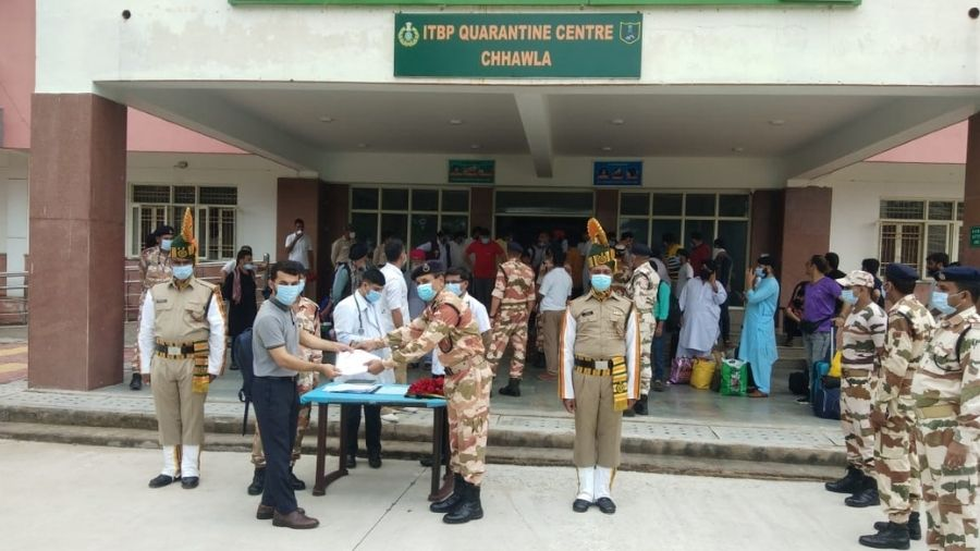An ITBP official hands over medical certificate and a rose to an evacuee on Tuesday in New Delhi