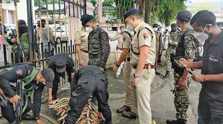 Security personnel  collect the knives deposited at the  gate of the secretariat in Shillong by the leaders of the pressure groups from Mawlai on Friday