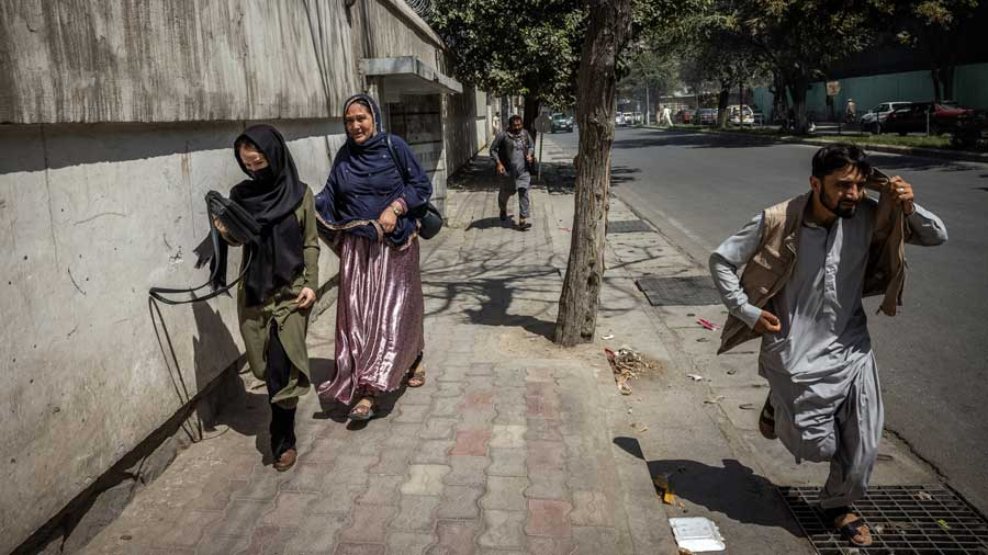 Women and men flee the scene of a protest after Taliban forces broke it up in Kabul, Afghanistan, on Tuesday, Sept. 7, 2021. The Taliban's response to the latest demonstration by women in Kabul was another sign that they will not tolerate peaceful dissent in Afghanistan.