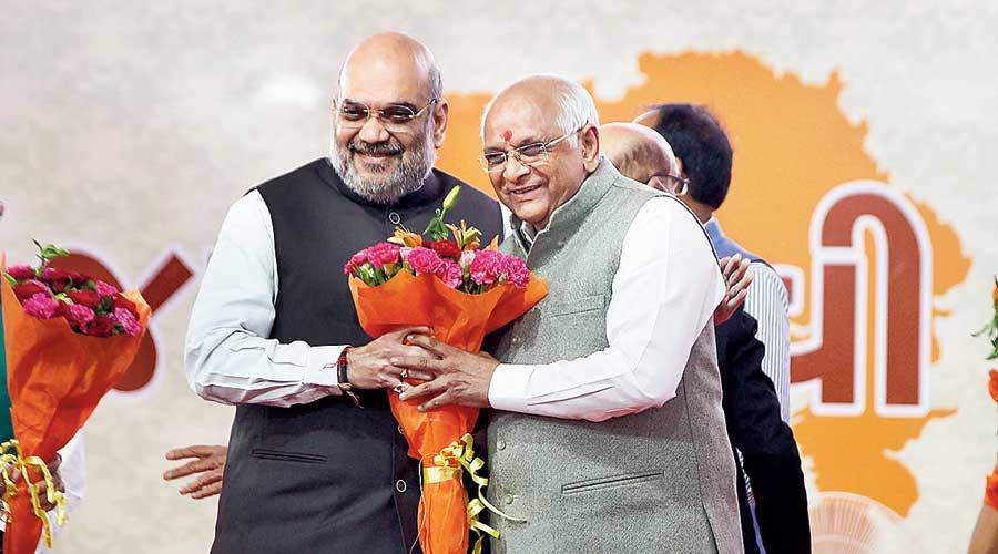 Amit Shah congratulates new Gujarat chief minister Bhupendra Patel at the swearing-in ceremony at  Raj Bhavan in Gandhinagar on Monday