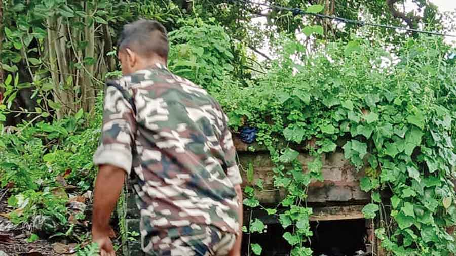 A policeman searches a bush near Arjun Singh's residence at Jagaddal on Tuesday.