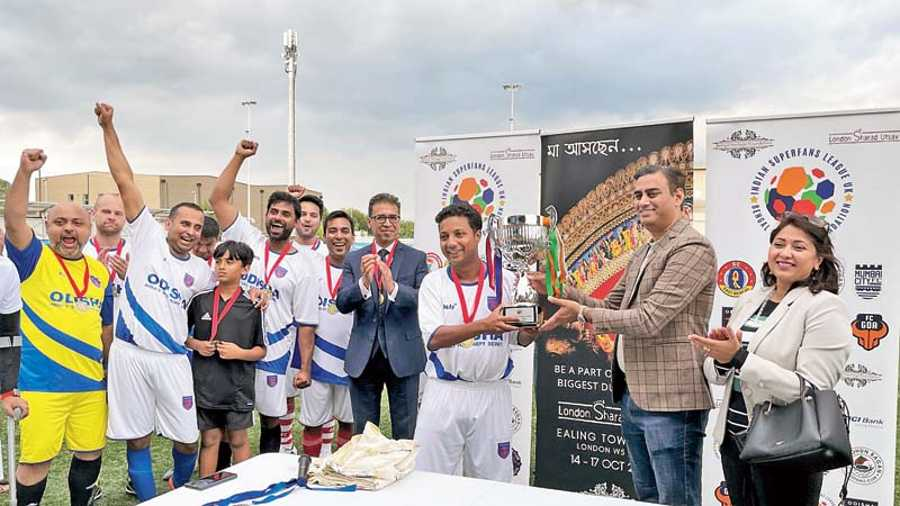Rohit Vadhwana, first secretary, Indian High Commission in the UK, handing over the winner's trophy to Deep Ratan Sarkar, captain of Odisha FC Superfans as the rest of the team cheers. Also seen applauding in the picture is Raj Athwal, the president of Odisha FC