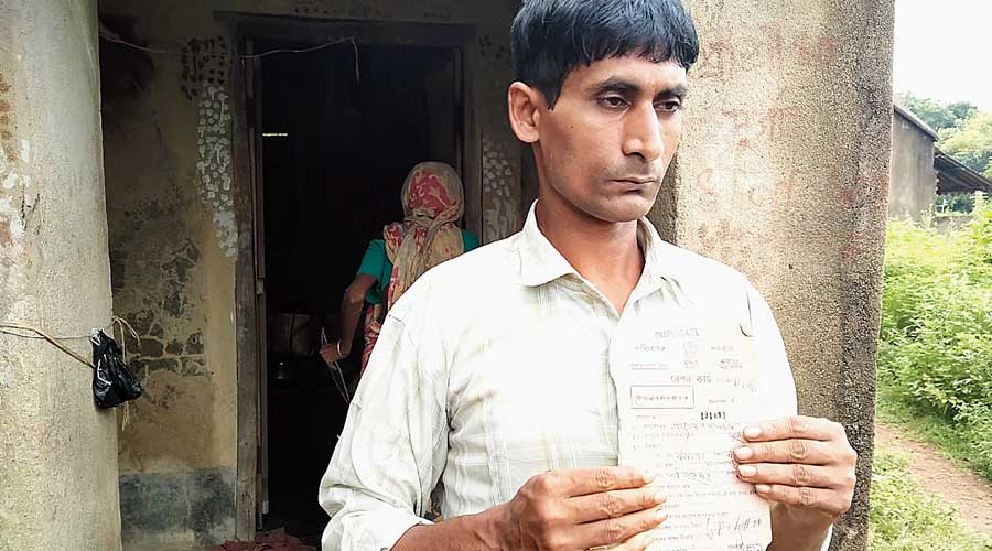 Gangadhar Pramanik with his ration card in front of his house on Thursday