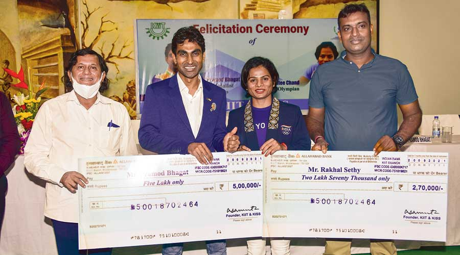KIIT founder Achyuta Samanta (left) hands over cheques to Pramod Bhagat (second from left) and Rakhal Sethy on Monday. Dutee Chand is second from right