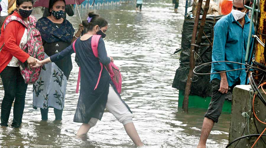 Commuters cross a flooded stretch of College Street