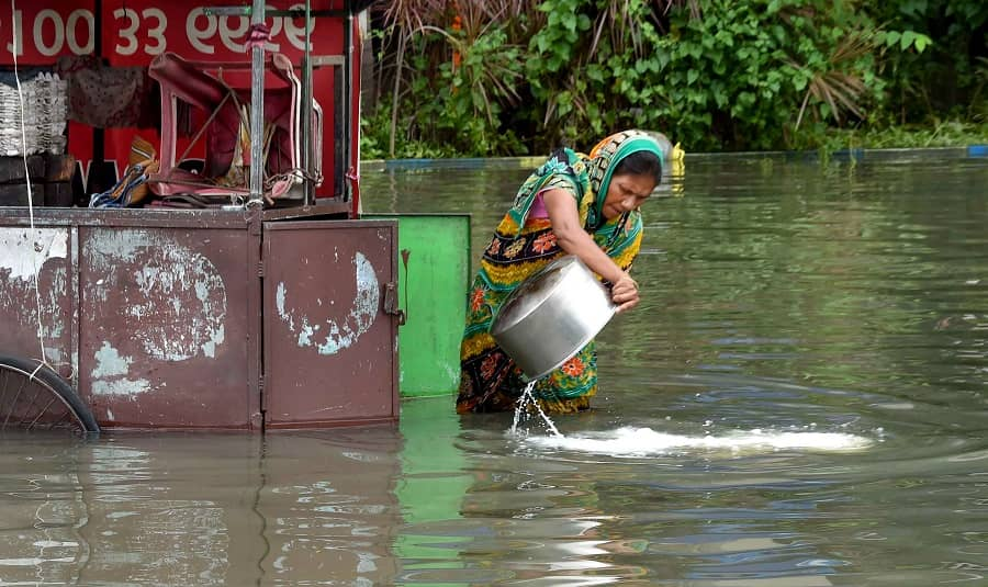 A woman throws milk on a waterlogged road from her tea stall after heavy rains in Kolkata on Tuesday.