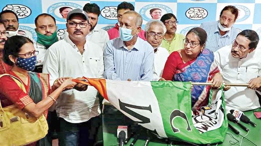 (From left) New entrants Sharmila Das and Tapas Chatterjee with Gautam Deb and the Trinamul flag.