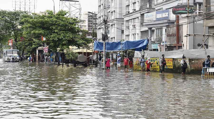 Pedestrians wade through a flooded road in Chinar Park around noon on Tuesday.