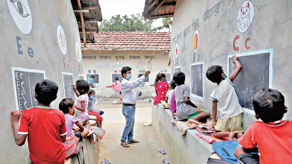 Deep Narayan Nayak, 34, a teacher, teaches children, who do not have access to internet facilities and gadgets, in an open air class outside the houses with the walls converted into black boards following the closure of their schools due to the coronavirus disease (COVID-19) outbreak, at Joba Attpara village in Paschim Bardhaman district in the eastern state of West Bengal, India, September 13, 2021.
