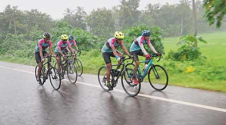 The team cycles through rain