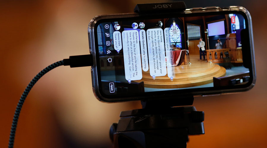FILE -- An Apple iPhone plugged into a Lightning connector cable is used to stream a church service in Chapel Hill, N.C., March 15, 2020.