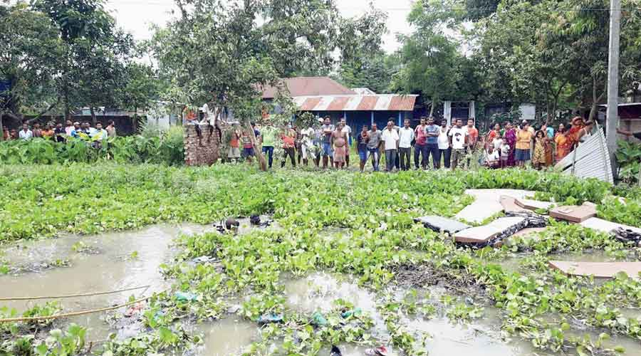 Residents watch divers search the ditch at Rupahar near Raiganj on Thursday morning.