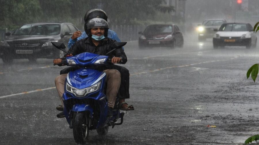 A scooterist and his pillion rider are caught in sudden rain in Kolkata on Thursday afternoon.