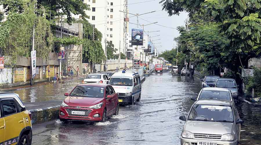 Vehicles ply through a waterlogged stretch in front of the Avidipta housing complex in Mukundapur.