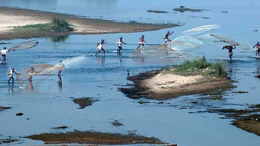 Community fishing on the Shilabati river.