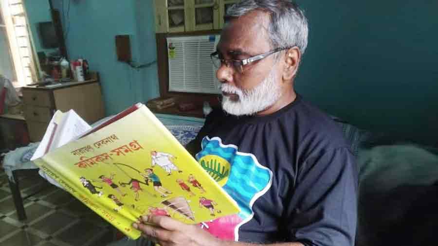 Cartoonist Debasish Deb, immersed in a Narayan Debnath book