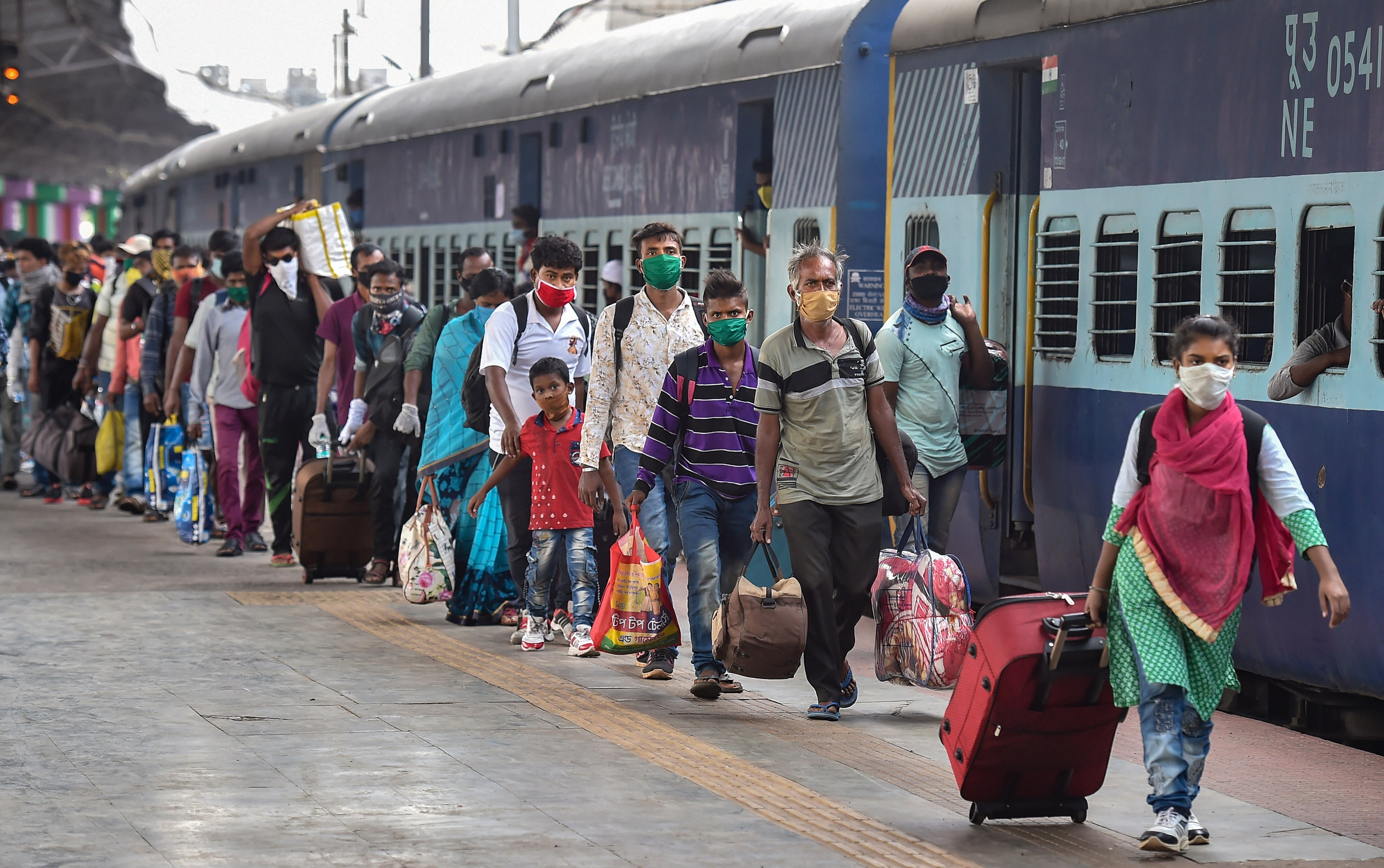 Migrants walk in a queue after deboarding a special train at Howrah station in Calcutta on Monday