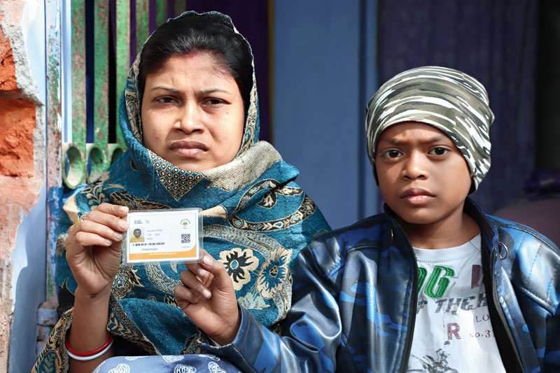 Sagar Patro's mother Anita holds his Ayushman Bharat card as his brother Ayush looks on at their house in Golpahari, Parsudih, on Tuesday.