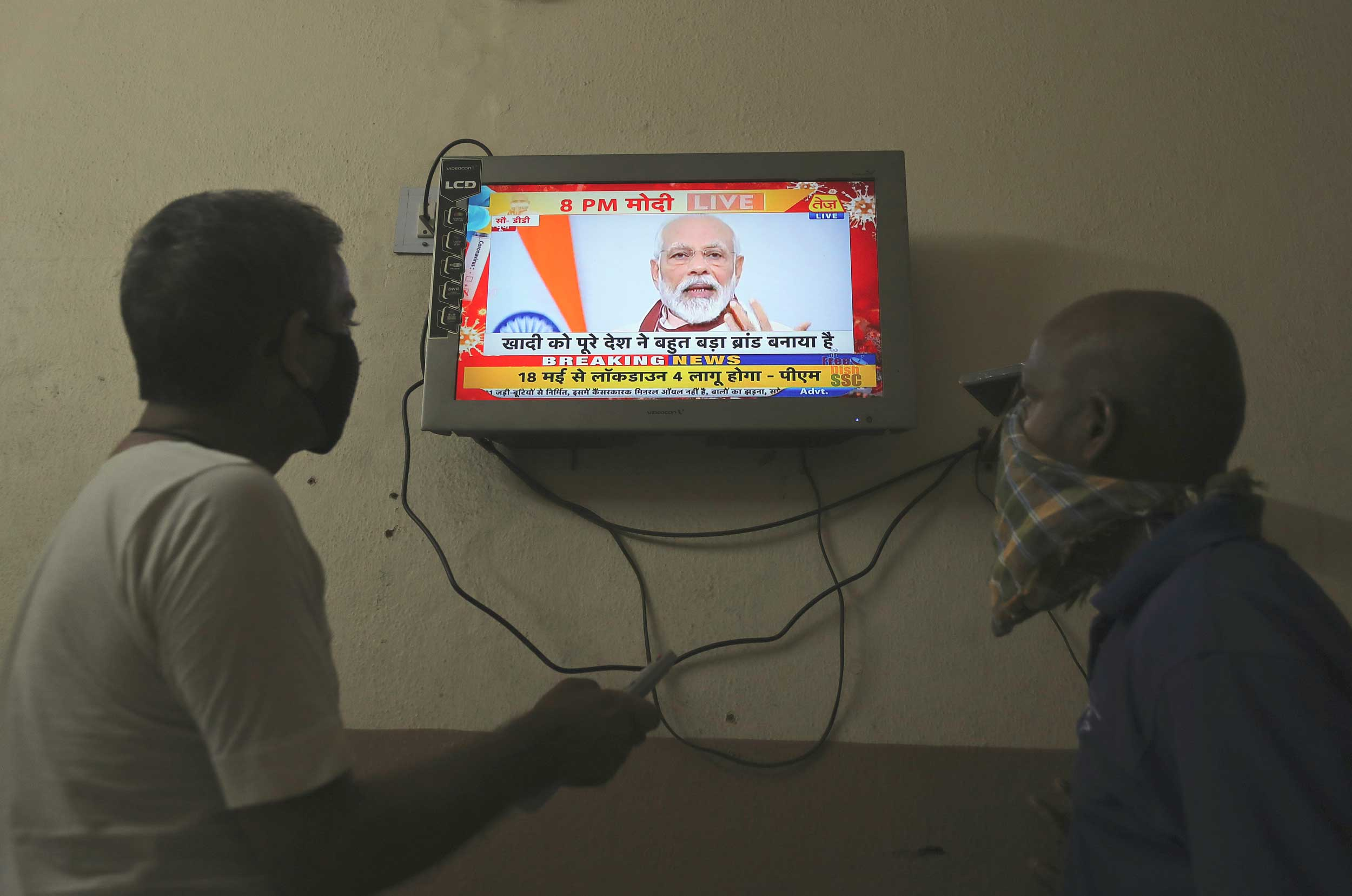 Two men watch a televised Prime Minister Narendra Modi's address to the nation in Hyderabad on Tuesday.