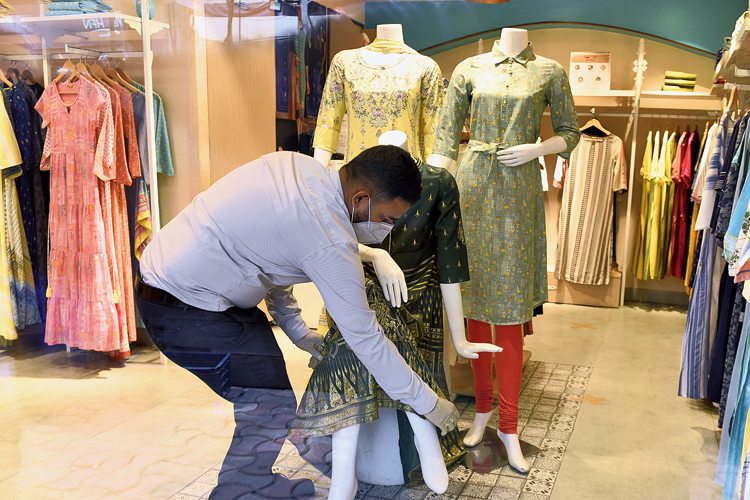 A man adjusts the dress of a mannequin at a shop in New Market on Sunday.