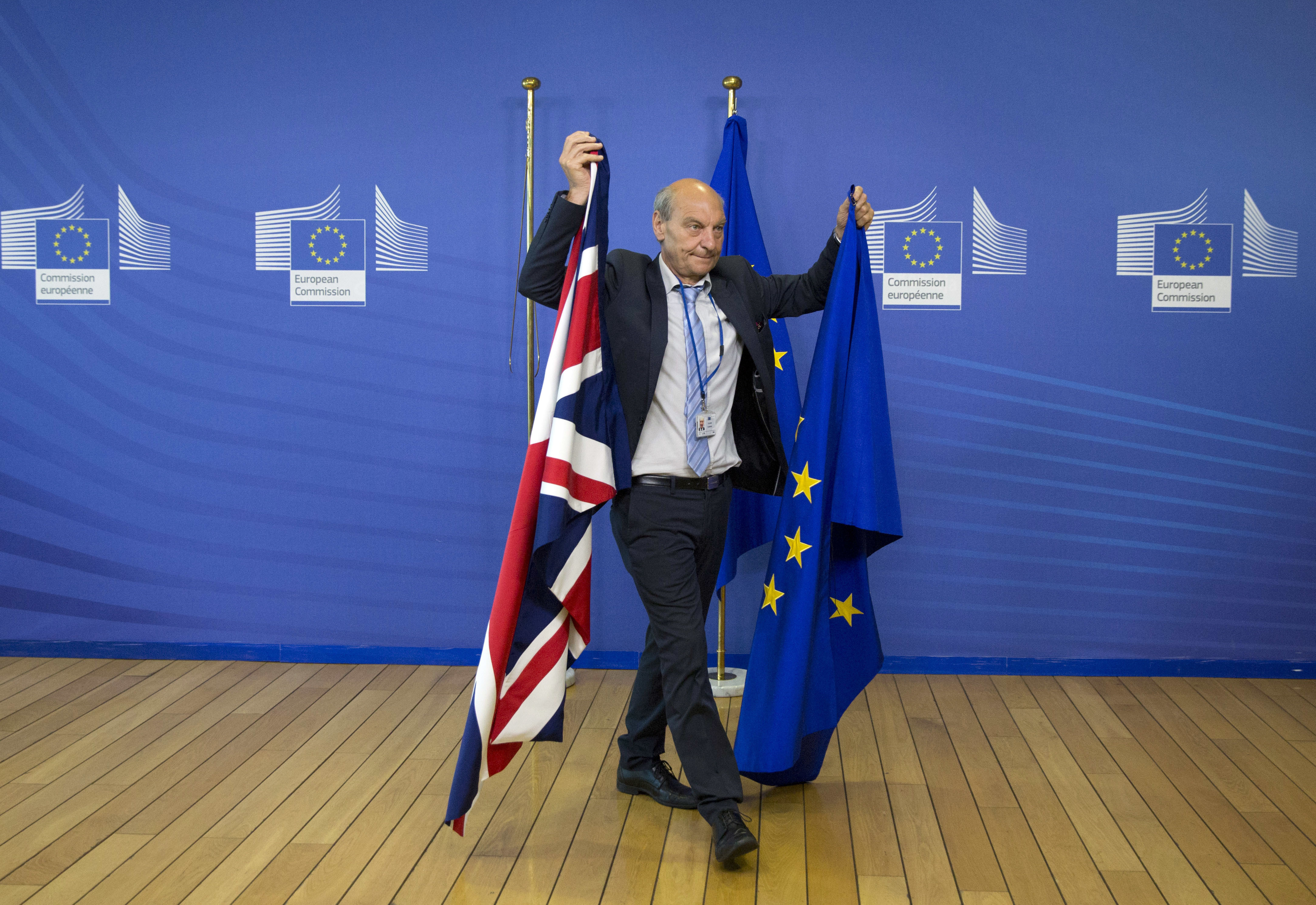 In this June 19, 2017, file photo, a member of protocol changes the EU and British flags at EU headquarters in Brussels. On Tuesday, January 15, 2019, British lawmakers overwhelmingly rejected Prime Minister Theresa May's divorce deal with the EU plunging the Brexit process into chaos
