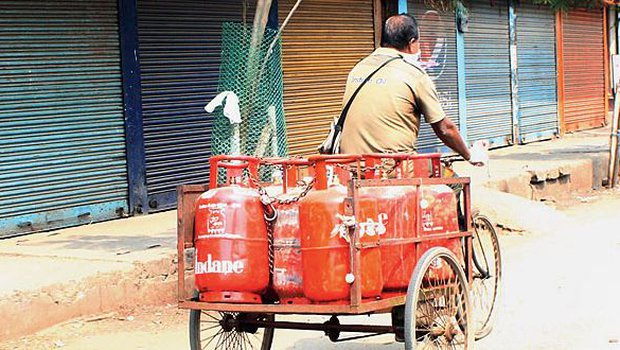 A delivery man carries LPG cylinders in Guwahati