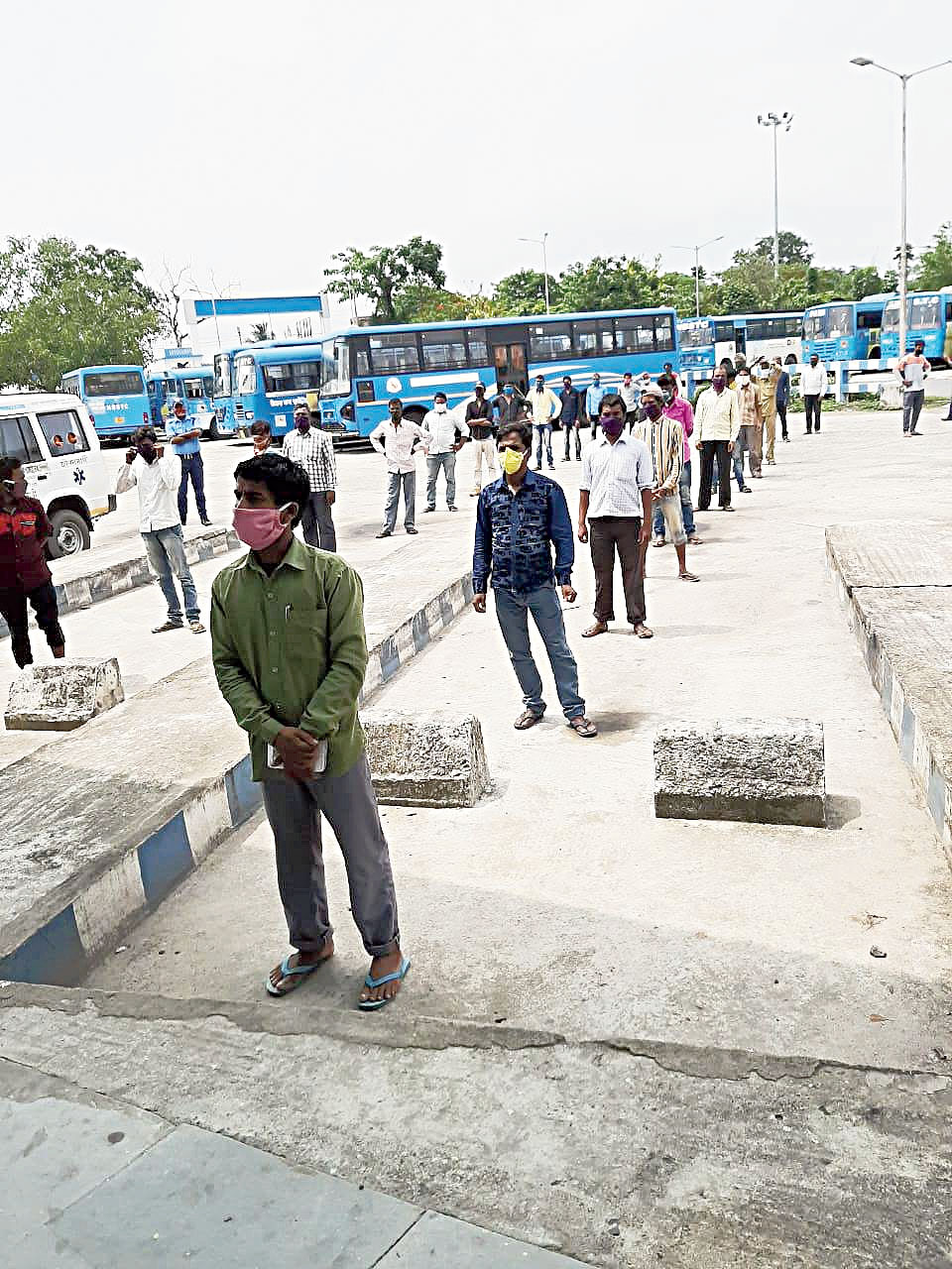 Migrants stand in a queue at a bus terminus in Malda on Monday