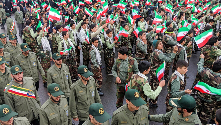 School students wave their national flags as Revolutionary Guard members arrive in Azadi, freedom square, during a ceremony celebrating the 40th anniversary of Islamic Revolution, in Tehran on Monday, February 11, 2019.