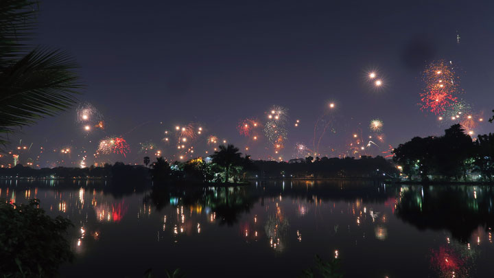 Star-studded: The night sky lit up by fireworks is reflected in Rabindra Sarobar on Sunday night