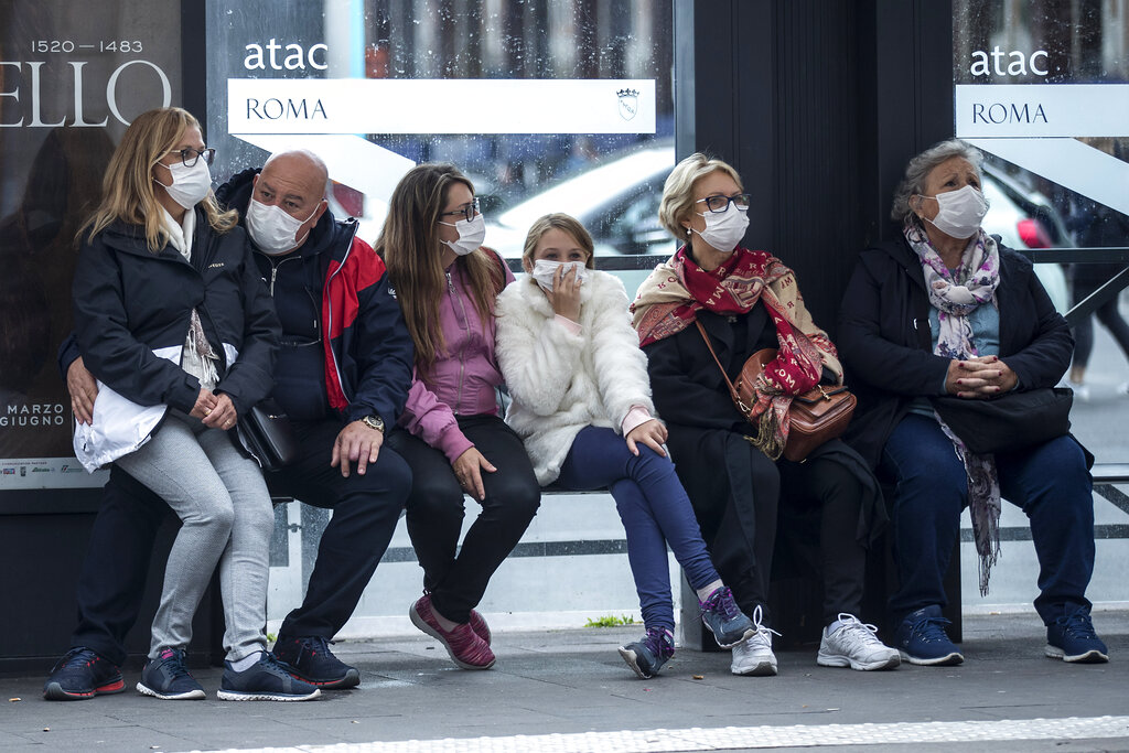 People wait at a bus stop, in Rome, Monday, March 9, 2020. Italy announced a sweeping quarantine early Sunday for its northern regions, igniting travel chaos as it restricted the movements of a quarter of its population in a bid to halt the new coronavirus' relentless march across Europe.