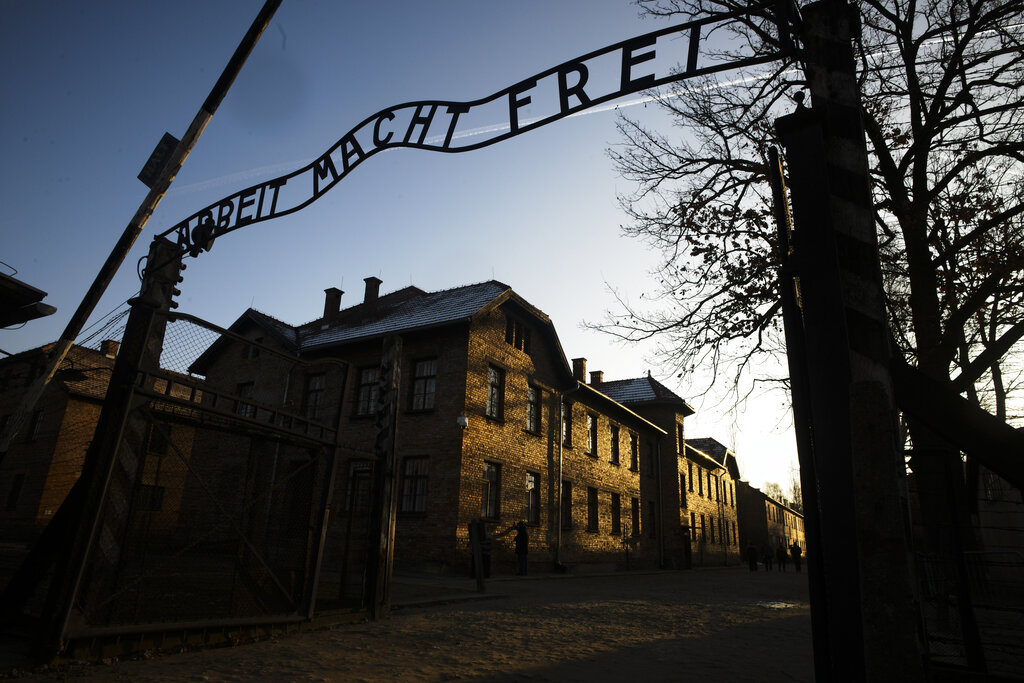 In this December 6, 2019, file photo, the sun lights the buildings behind the entrance of the former Nazi death camp of Auschwitz-Birkenau in Oswiecim, Germany.