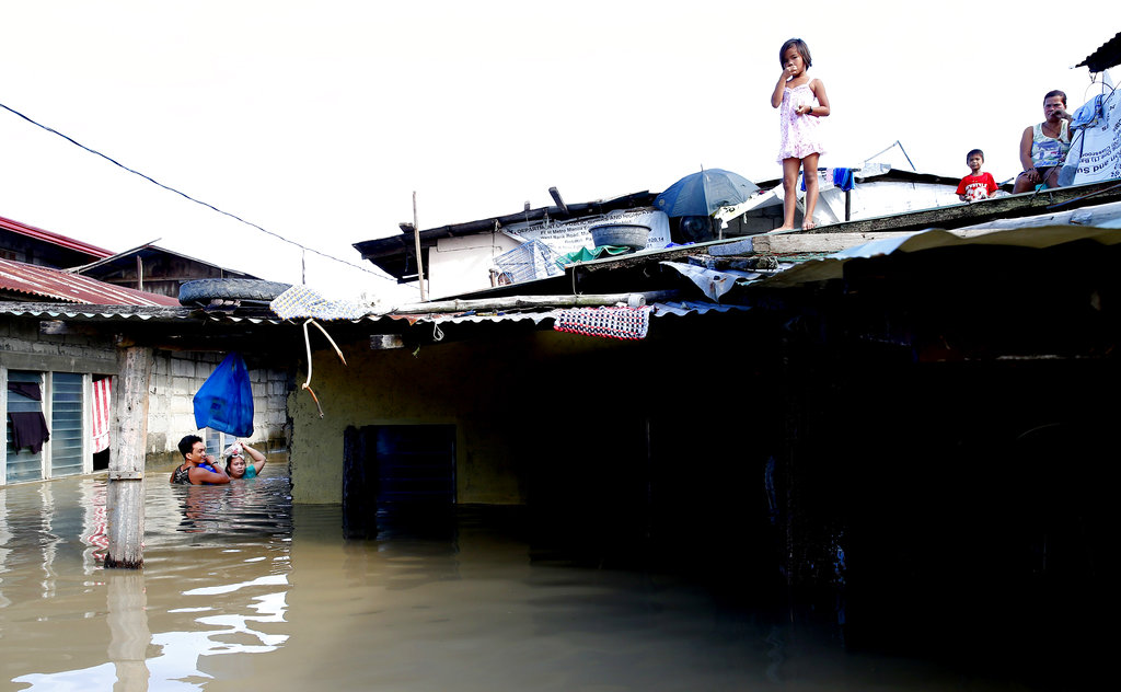 A couple wades through water as a girl watches from a rooftop following flooding brought about by Typhoon Mangkhut, which barreled into northeastern Philippines.