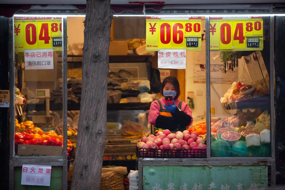 A clerk wearing a face mask waits for customers at a fruit shop in Beijing on February 29