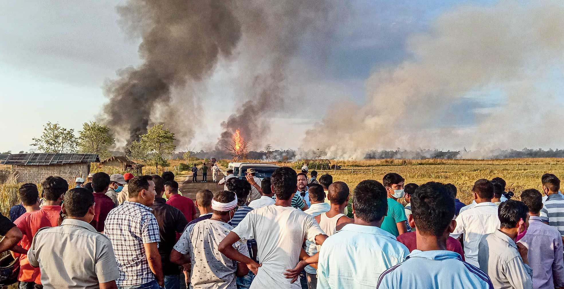 Residents look on as smoke rises from the fire at Baghjan oil field.