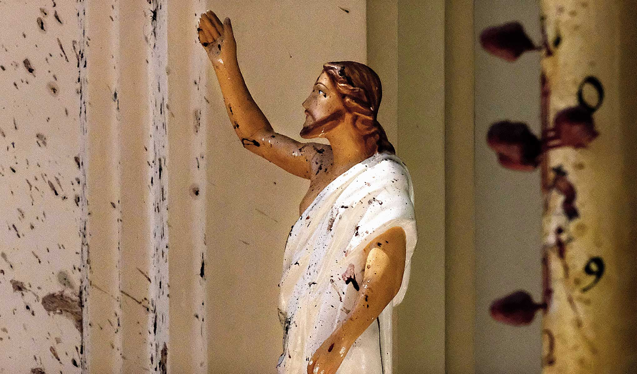 Bloodstains are seen on the wall and on a Jesus Christ statue at the St Sebastian's Church at Negombo, north of Colombo, where dozens were killed.