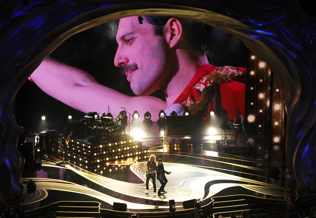An image of Freddie Mercury appears on screen as Brian May, left, and Adam Lambert of Queen perform at the Oscars. Rami Malek, who played Mercury, won Best Actor.