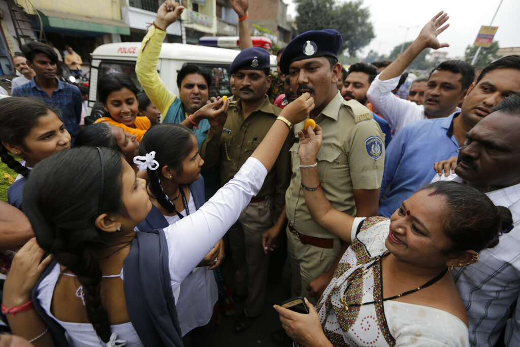 People feed sweets to policemen on duty and shout slogans in favor of police to celebrate killing of four men suspected of raping and killing a woman in Shadnagar in the southern state of Telangana, in Ahmadabad, on Friday, Dec. 6, 2019.