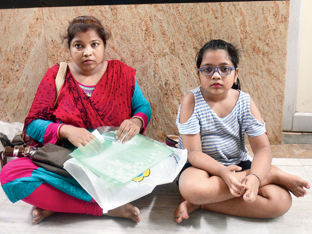 """Rama Shaw, a Howrah homemaker, and her eight-year old daughter Srija sit on the floor of the outpatient department at SSKM Hospital as they wait for the doctor around 10am on Wednesday. """"My daughter was scheduled to get an MRI scan done. I had to show the report to a doctor,"""" said Rama. She could do neither. She did not know the name of the doctor and described him as a """"surgeon"""". She said the doctor was not there. The two left after waiting for over an hour."""